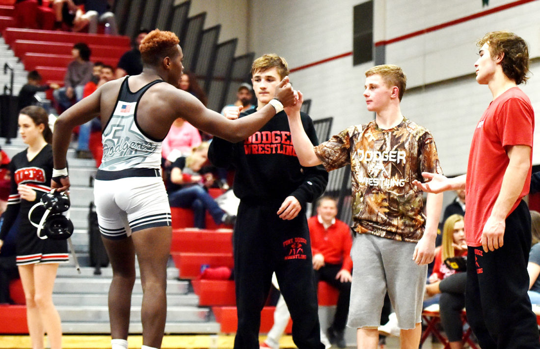 Messenger photo by Britt Kudla  Fort Dodge wrestlers (left to right) Drew Bennett, Brody Teske and Cayd Lara greet Dorian Franklin after a match earlier this season.