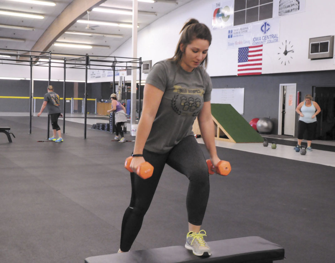 -Messenger photo by Joe Sutter  Liz Raasch steps up and down during one portion of a workout while others run or swing weights at the Tuesday class at the REC Coliseum.