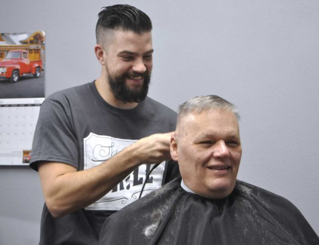 -Messenger photo by Chad Thompson  Phil DeCastro, owner of The Drill Barbershop, and Ron Hedeen, of Fort Dodge, share a laugh at the Fort Dodge shop recently.