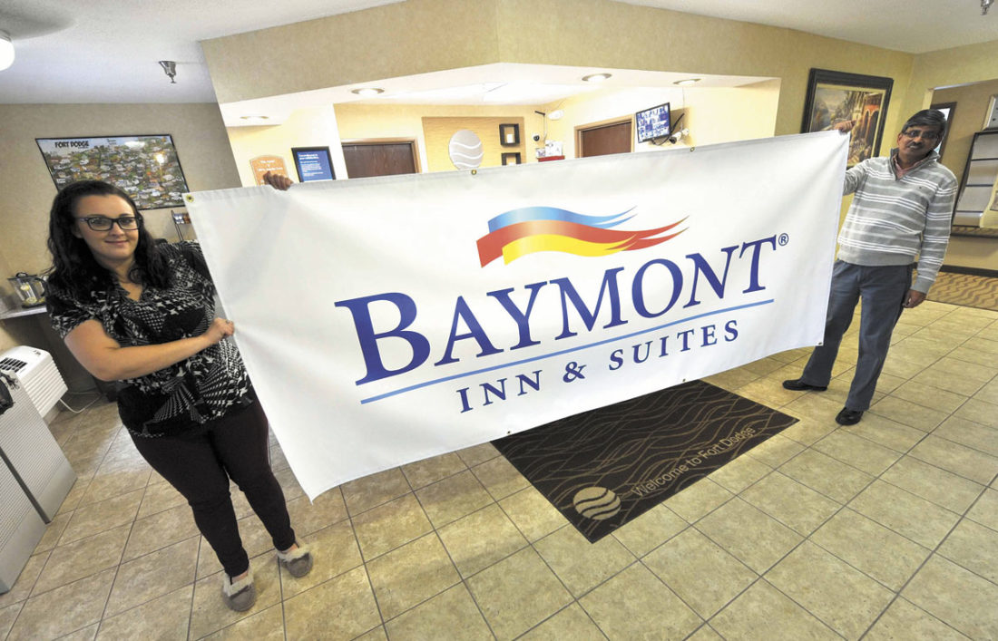-Messenger photo by Hans Madsen  Baymont Inn & Suites owner Paresh Bhatt, at right, along with general manager Whitney Faulkner, hold up a banner that was used to help rebrand the hotel. It is located at 2938 Fifth Ave. S. in Fort Dodge.