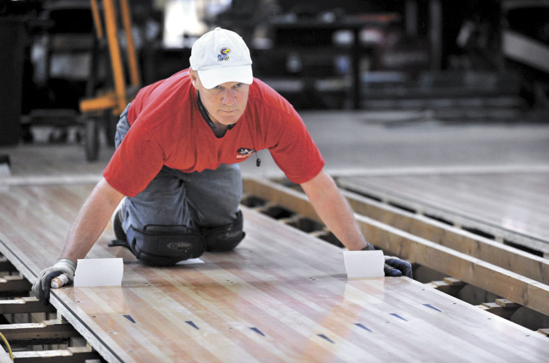 -Messenger photo by Hans Madsen  Craig Bastemeyer, co-owner of Cubica AMF, of Lawrence, Kansas, makes sure one of the new lane panels is lined up perfectly as he works on replacing the lanes at Family Bowling Center in Fort Dodge.