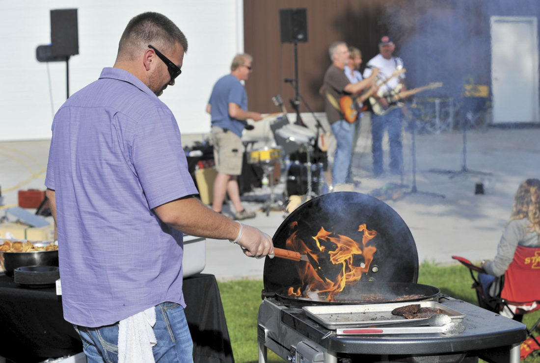 -Messenger photo by Hans Madsen  Tom Bollig, with Infinity Restaurant Group, cooks up a batch of burgers recently during an evening at the Soldier Creek Winery northeast of Fort Dodge as the Kris Karr Band plays for visitors.