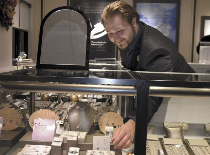 -Messenger photo by Chad Thompson  Derek Sweeney, a store employee, reaches for some diamond fashion rings at the newly opened Kay Jewelers in Fort Dodge recently. Sweeney, of Manson, began working at the store when it opened Nov. 11, 2016.