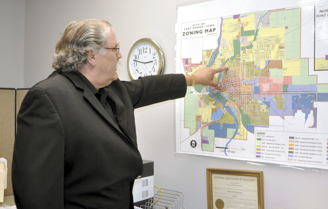 -Messenger photo by Chad Thompson  James Kesterson, president of Kesterson Realty Inc., points out a location on a Fort Dodge zoning map at the firm's new location.