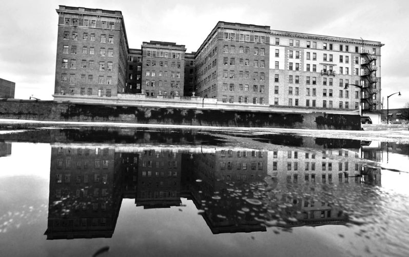 -Messenger photo by Hans Madsen  The Warden Plaza, along with its reflection in a pool of meltwater atop a roof across the street, is shown on an overcast winter day. A project to rehabilitate the former hotel, apartments and shops is in the works.