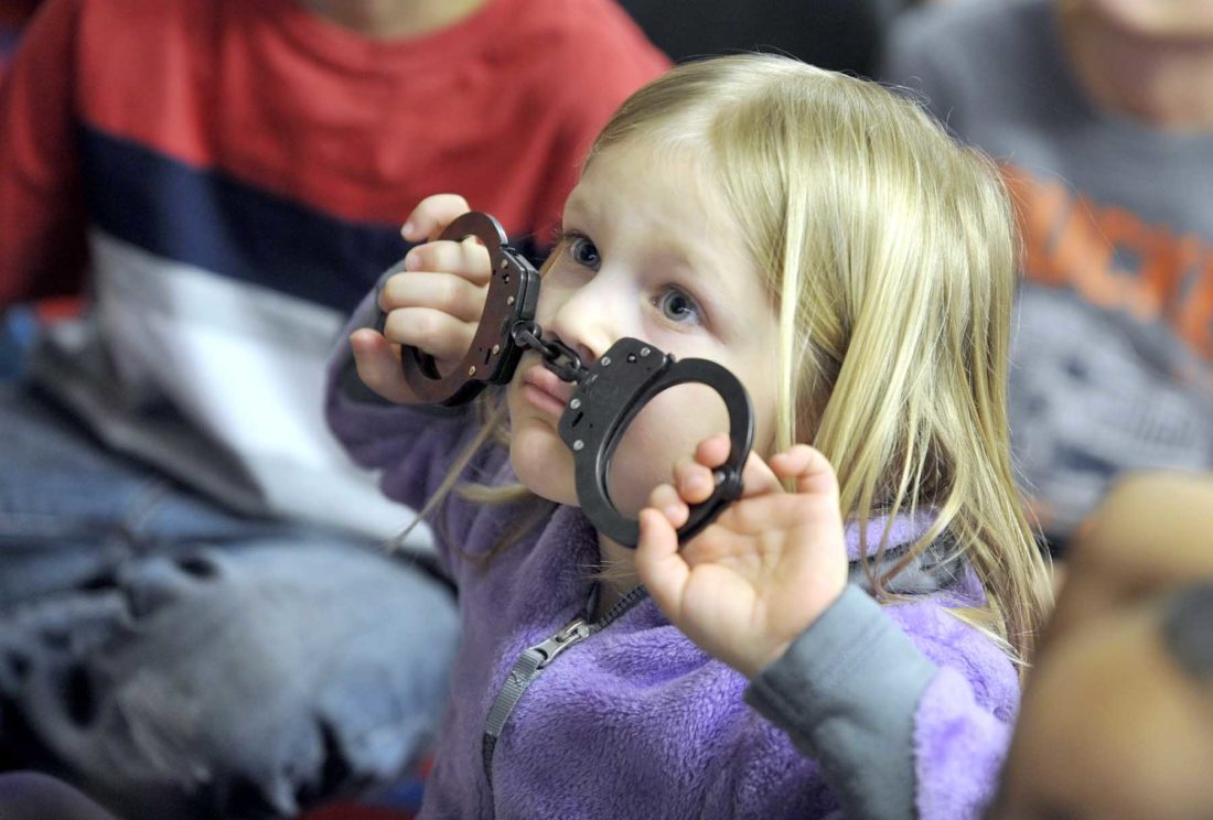 "-Messenger photo by Hans Madsen  Greyson Hinds, 6, a kindgergarten student at Cooper Elementary School, creates a ""CuffStache"" with Fort Dodge Police School Resource Officer Cody Harris' handcuffs Thursday morning while he read them a book about being a police officer. The book reading, by people with a variety of careers, is part of a Me and My Community the children are exploring with teacher Jen Yoder. Harris let the children examine the handcuffs while he answered questions."