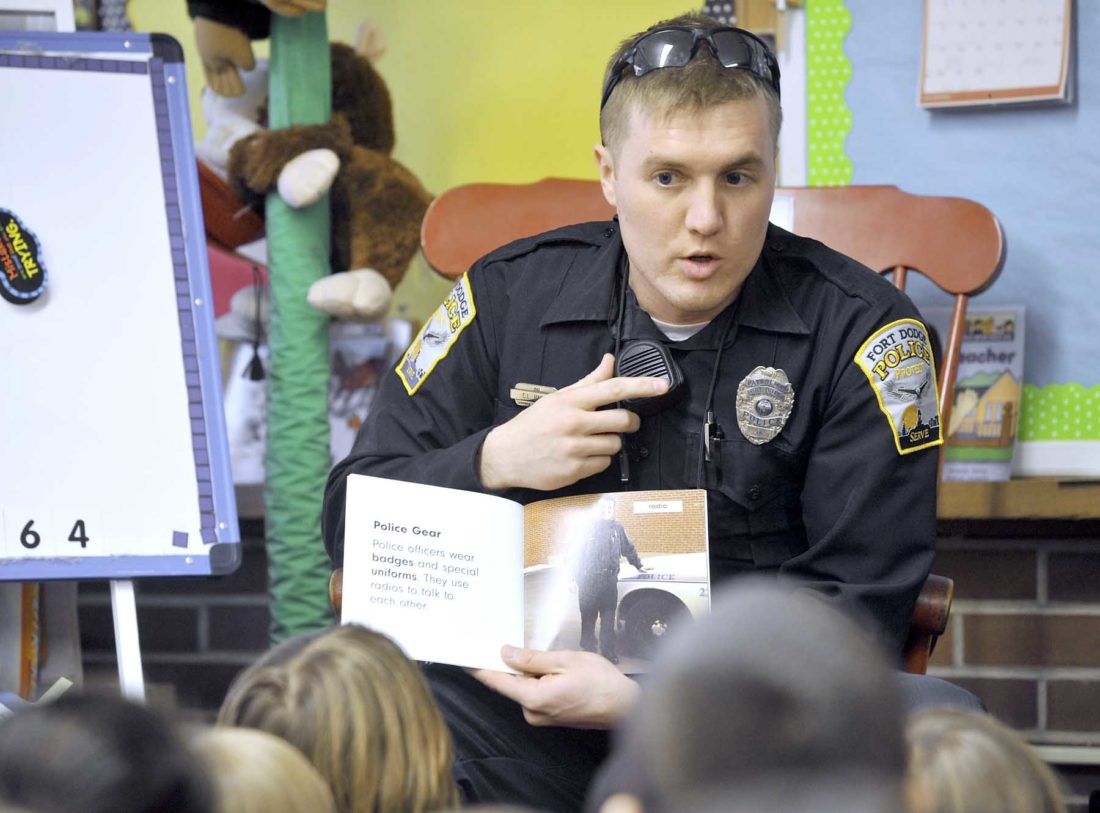 -Messenger photo by Hans Madsen  Fort Dodge Police Resource Officer Cody Harris shows the Cooper Elementary School students the radio microphone clipped to his uniform shirt Thursday morning while reading a book about being a police officer to the students.