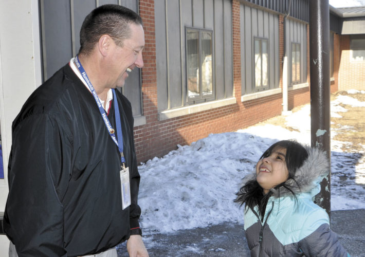 -Messenger photo by Chad Thompson  Alexis Valencia, 8, right, shares a moment with Principal George Bruder at Taft Elementary School recently. A new expansion to the school will encompass the area where Bruder and Valencia are standing.