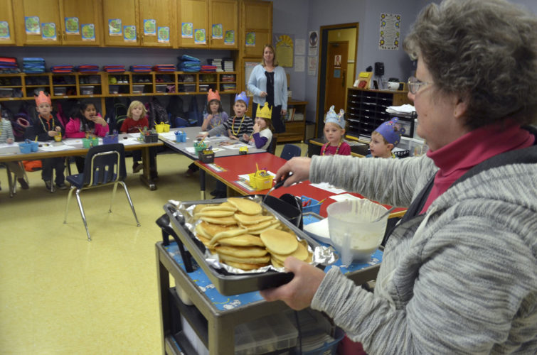 -Messenger photo by Joe Sutter  On a recent February afternoon, Roxanne Schuur celebrates the 100th day of school this year by cooking up pancakes for her kindergarten class at St. Paul Lutheran school, while principal Julie Mann looks on.