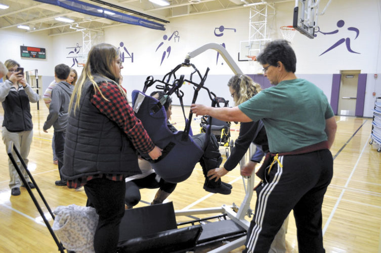 -Photo by Billie Shelton  Webster City High School special education teacher Amanda Nichols, left, and Webster City High School physical education teacher Catherine Schroeder place one of Nichols' students in a specially made scooter during Peer P.E. during the 2016 fall semester. The scooter was built by students in Ben Jass' class.