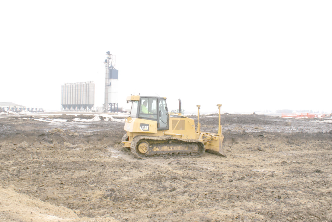 - Messenger photo by Dawn Bliss  A bulldozer moves dirt Feb. 7 where the new pelletmill will be built at NEW Cooperative's location near Rowan. The structure in the backgroun is part of the NEW's new fertilizer plant which started operations in 2016. The mill is expected to be operational in 2018.