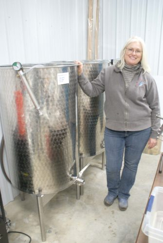 -Messenger photos by Dawn Bliss Mary Haverkamp poses in the winery of her Kossuth County farm, where vinifies 13 different types of wine using grapes from her vineyard and from neighboring grape growers.