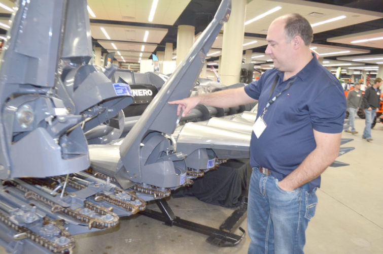 -Photo by Larry Kershner  Craig Yeager, a salesman for GBC Distributing, points out the conical underbelly of the snoots on this Mainero MDD-100 corn head allows a combine operator to harvest in any corn field regardless of row width and direction.