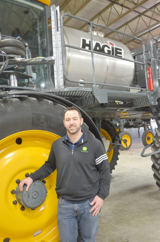 -Photo by Kriss Nelson  Luke Kerns, with John Deere, poses beside a sprayer in Hagie's manufacturing plant in Clarion.