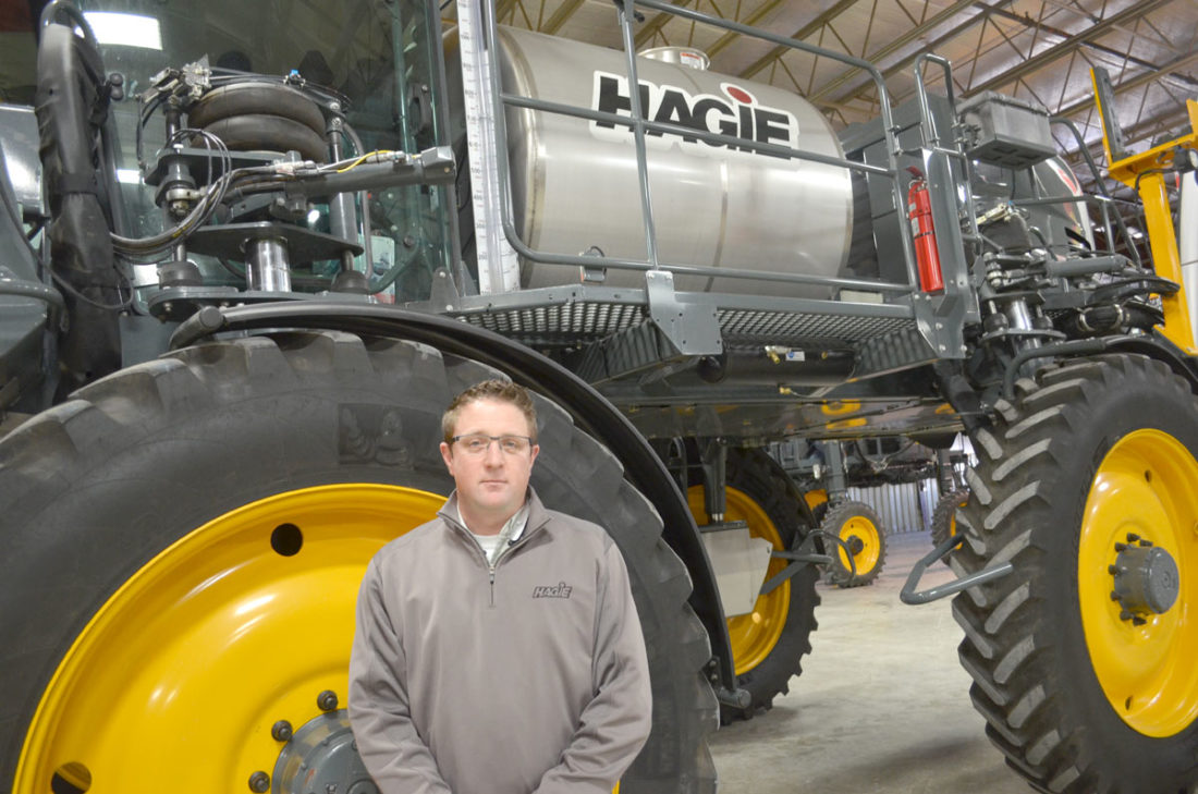 -Photo by Kriss Nelson  Kevin Marshall, product line manager with Hagie Manufacturing, poses beside a sprayer in Hagie's manufacturing plant in Clarion.