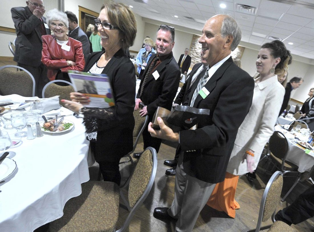 -Messenger photo by Hans Madsen  Bruce Shimkat is all smiles Thursday night after receiving the annual Catalyst Award during the Greater Fort Dodge Growth Alliance's annual dinner. His wife, Sally, at left, along with family members and friends, helped him celebrate.