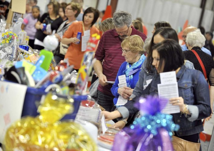 -Messenger photo by Hans Madsen  Potential buyer walk up and down the rows of cakes available in the silent auction during the 21st annual Domestic/Sexual Assault Outreach Center Cake Auction held in 2016 at the Iowa Central Community College East Campus Saturday evening.