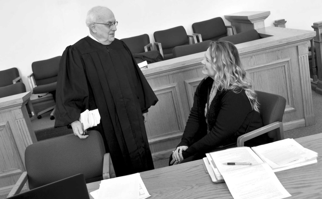 -Messenger photo by Hans Madsen  After posing for his portrait, retired judge Al Habhab stops to visit with Roni Yetmar-Henry, a probation/parole officer, during a session of the District Court's Drug Court.