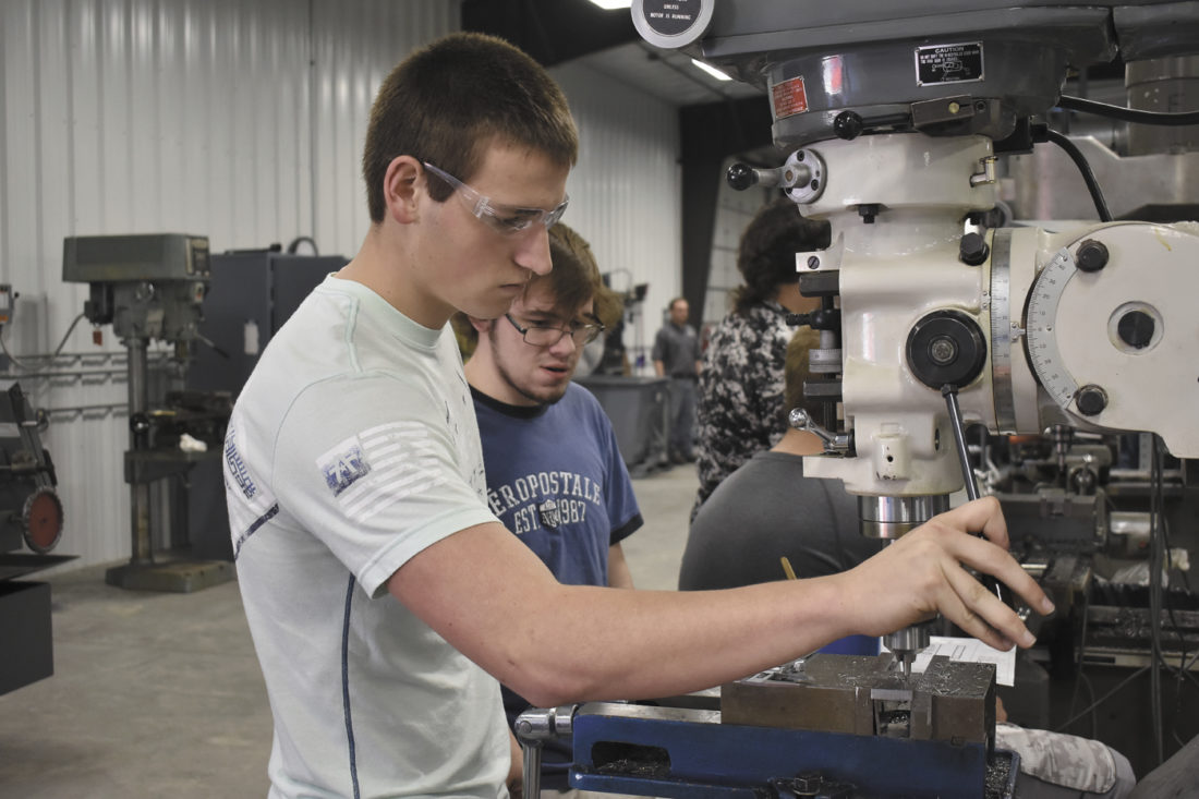 -Messenger photo by Chad Thompson  Mason Bauer, 18, a senior at Webster City High School, gets to work on a milling project at the North Central Career Academy. Hunter Dixon, 18, also a senior at Webster City High School, looks on.