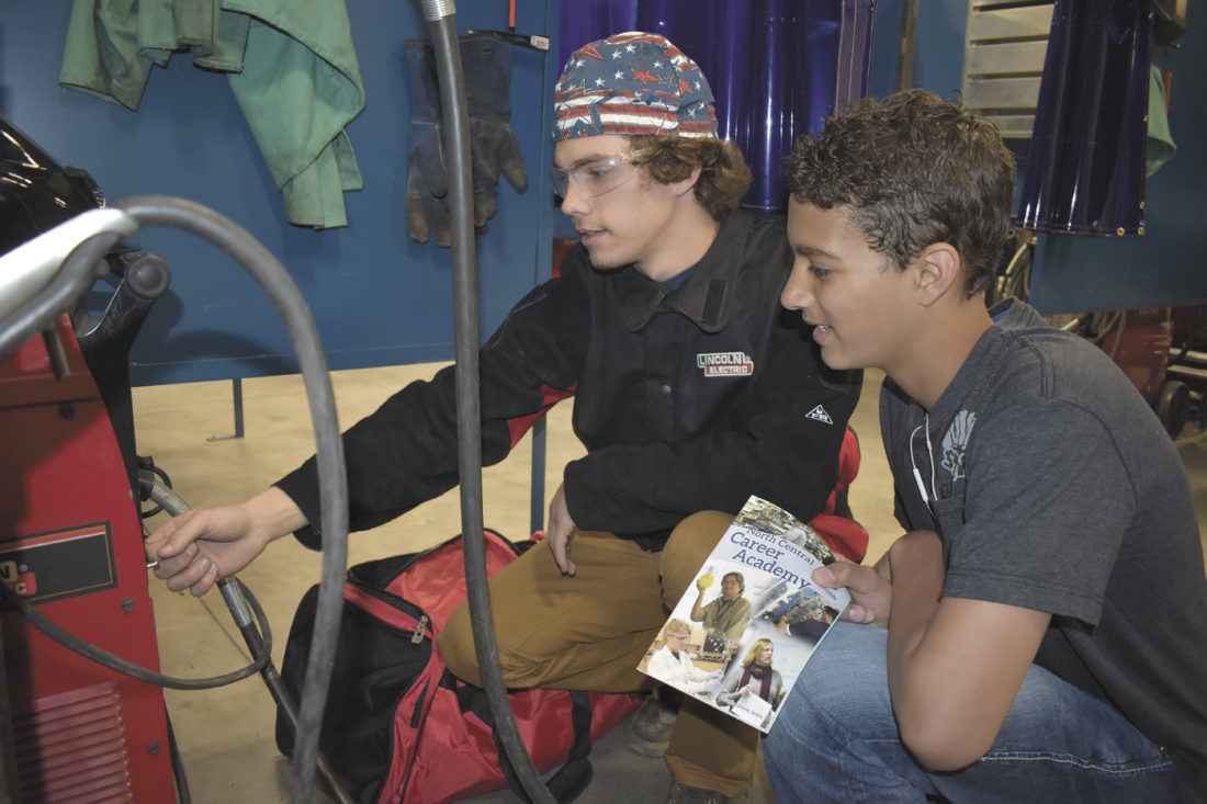 -Messenger photo by Chad Thompson  Ozzy Pattison, 18, a senior at Fort Dodge Senior High, left, shows Izaih Clark, 16, a sophomore at FDSH the settings on a welder at North Central Career Academy in Eagle Grove Monday morning.