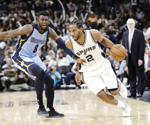 AP Photo  San Antonio forward Kawhi Leonard (2) drives around Memphis player James Ennis III on Monday night.