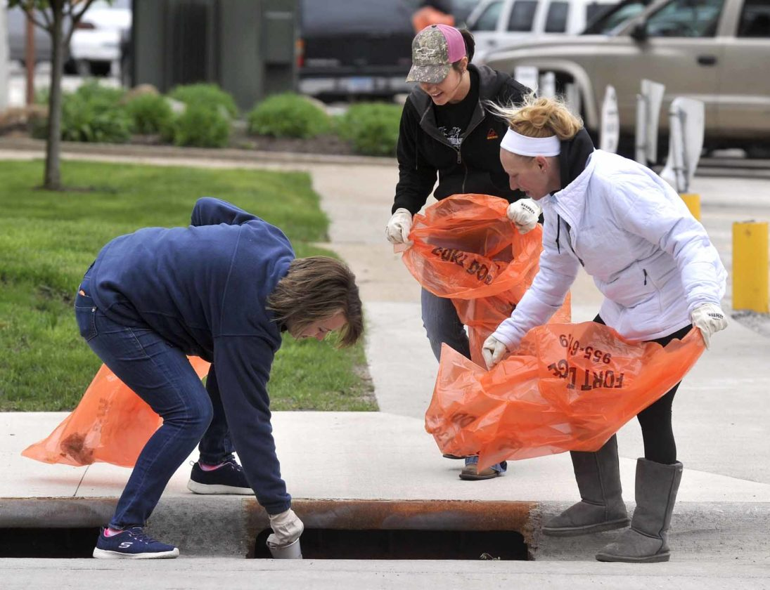 -Messenger photo by Hans Madsen  Volunteer Courtney Bachel, at left, works to recover a drink cup from the storm sewer inlet in front of the Fort Dodge Municipal Building during the annual FOD Walk. Her Decker Truck Line Inc. coworkers Megan Kruse, center, and Peggy Cloud, right, stand by with bags. They were joined by fellow worker Teresa Otto.