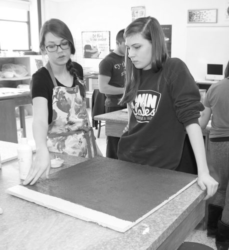 Jenny Bonnall and student Keely Hammen pointers about blending colors on her tile. Bonnall and her Advanced Painting students at South Central Calhoun High School created art for patient rooms at Stewart Memorial Community Hospital.