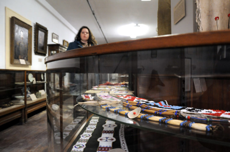 -Messenger photo by Joe Sutter  Veronica Guyader explains how this half of the east exhibit hall has been reorganized, including these artifacts crafted by Sumner Heman, member of the Makawain Indian Lore club, based on traditional Plains Indian designs, materials, and techniques. The hall now includes more narrative about Native American treaties with the U.S. and the process by which natives were pushed west, giving background on the creation of the original fort and the Spirit Lake Massacre.