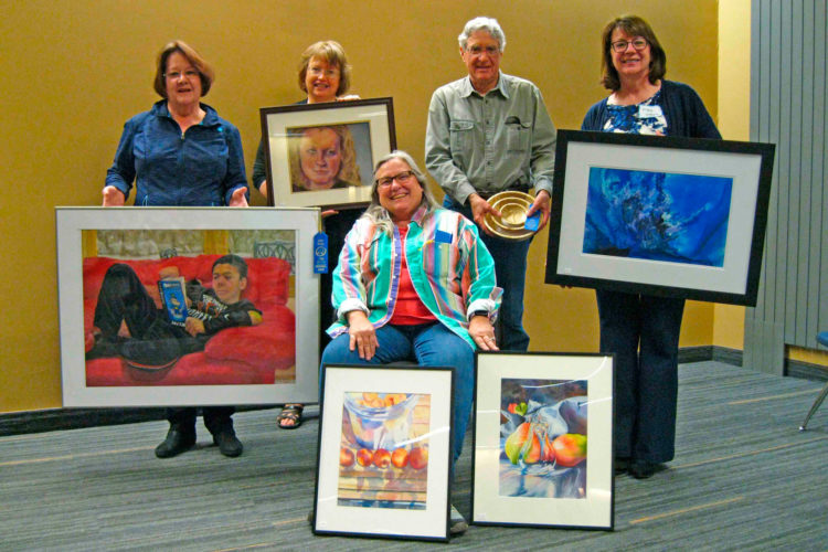 """Iowa Artists Region 5 held the annual Art Show at the Iowa Central BioScience and Health Sciences Building on April 8.  Blue ribbon winners are Gwen Foster (seated), Ankeny, one each for her watercolors, """"Apricots & Peaches"""" and """"Baciata dal Sole"""", and in back from left are Susan Colby, Clive, for her pastel """"Dogman Peydan""""; Delayne Segar, Fort Dodge, for her pastel, """"Makayla""""; Doyle Wilson, Boone, for his wood, """"Mom & Two""""; and Mary Johnson, Ankeny, for her watercolor, """"Tempest"""". The show was judged by Rusty Farrington, Iowa Central Community College art professor. The first-place blue ribbon winners advance on the the Iowa Artists State Show in Ames on May 13. Iowa Artists is a statewide group of artists with 12 regions.  Region 5 consists of Boone, Carroll, Polk, Webster, Greene, Guthrie, Calhoun and Dallas counties.   Red ribbon second-place winners are: Gwen Foster, Ankeny; Jeanine Carithers, West Des Moines; Rita Wheeler, Ogden; Jean Johnson, Boone; Delayne Segar, Fort Dodge; and Deborah Zisko, Boone. White ribbon third-place winners are Flo Hayes, Urbandale; Joan Sullivan, Fort Dodge; Susan Colby, Clive; Judy Wallace, Ogden; and Mary Johnson, Ankeny. Yellow ribbon honorable mention winners are Flo Hayes, Urbandale; Judy Wallace, Ogden; Jeanine Carithers, West Des Moines; Delayne Segar, Fort Dodge; Kathy Strohl, Madrid;  Mary Johnson, Ankeny;  Tom Holcomb, Adel; and Sharon Scandrett-Hipdon."""