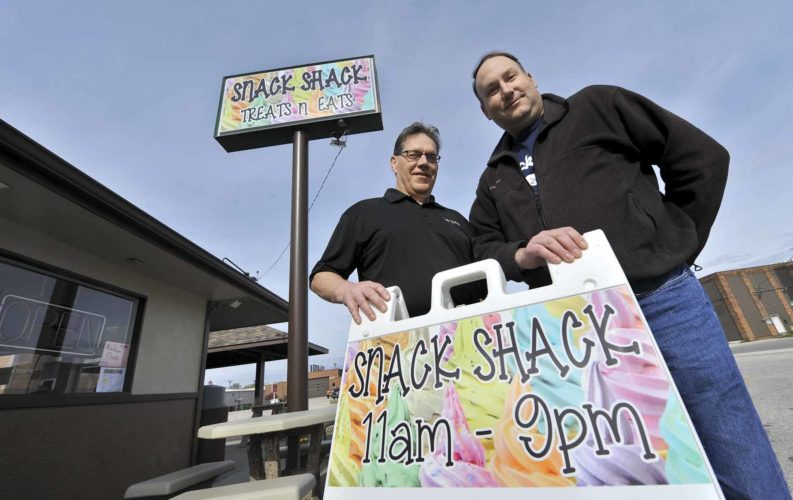 -Messenger photo by Hans Madsen  Snack Shack co-owners Steve Springer, at left, and Jason Kahler pose with the signs for their business recently. They opened April 1 and besides malts and shakes, also offer a selection of foods using fresh locally sourced ingredients. They are located at 11 S. 16th St. behind the Fire Station.