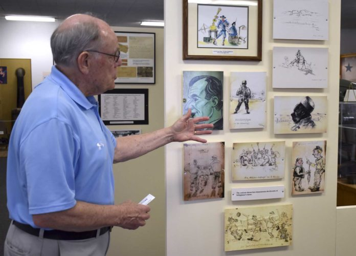 -Messenger photo by Chad Thompson  Jerry Yocum, vice president of the Camp Algona POW Museum, shares information about artwork created by German prisoners of war during World War II. The artwork to the far left in green is a caricature Harry Schippman drew of himself. Schippman was one of 10,000 German prisoners that made their way through the camp in Algona.