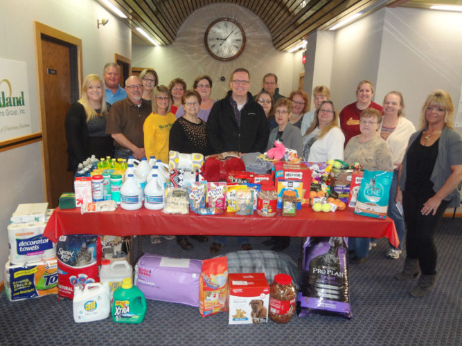 Heartland COMMUNICATIONS employees gathered contributions to Almost Home Animal Shelter.  Pictured in front are Amy Stanek, Rick Thomas, Cherri Miller, Maureen Anderson, Almost Home Director Chad Hammar, Sharen Egli, Leah Sargent, Donna Hogan and Karen Doyle. In the second row are Jon Berg, Carol Harrison, Pamela Schack, Sandra VanScoy, Sheila Davis, Laura Crowl, Wendy Sheldon, Katie Jordan and Julie Stark. Dave Gerdes is in the back.