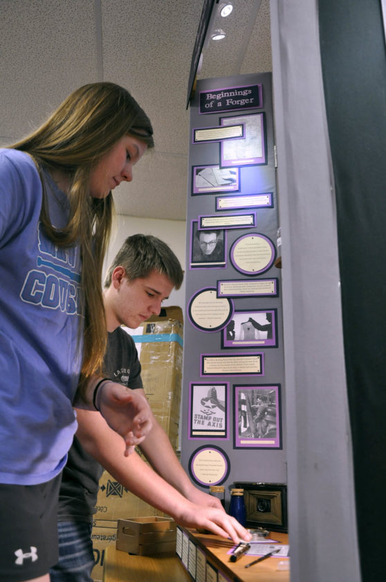 -Messenger photo by Joe Sutter  Julie Quade,left, (junior) and Matt Helmers, freshman, set up parts of their display on Adolfo Kaminsky, a forger in the French resistance during World War II. This presentation will have to stand on its own, without the students to explain it, at the National History Day competition in the Washington D.C. area.