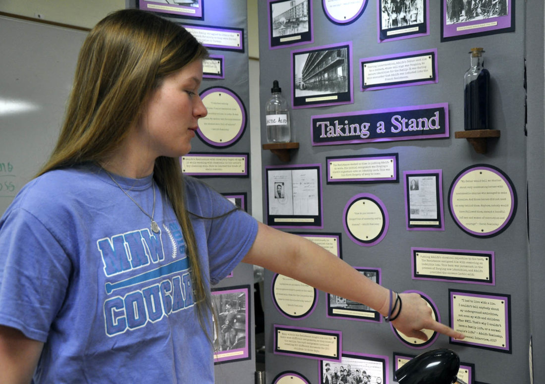 "-Messenger photo by Joe Sutter  Julie Quade, left, a junior, and Matt Helmers, a freshman, both Manson Northwest Webster students, look over their presentation for National History Day which won them a trip to the Washington, D.C.-area for the national competition. Their project, ""Adolfo Kaminsky: Forging For Freedom,"" tells the story of a forger in the French Resistance who saved the lives of countless Jewish people under the Nazi regime. It impressed the judges at both the regional and state level. This is Quade's third year going on to the national competition."
