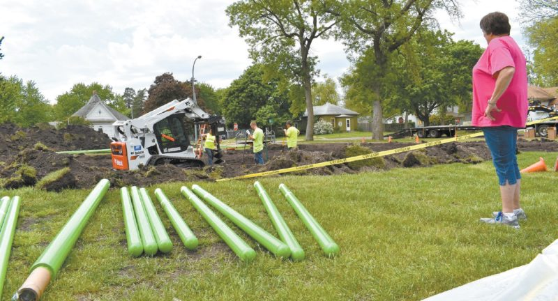 -Messenger photo by Chad Thompson  Sonna Johnson, a member of the Goldfield Women's Club, looks on as crews from SafetyFirst Playground Maintenance, of Princeton, Minnesota, work on getting the new equipment installed at Old School Park in Goldfield Monday.