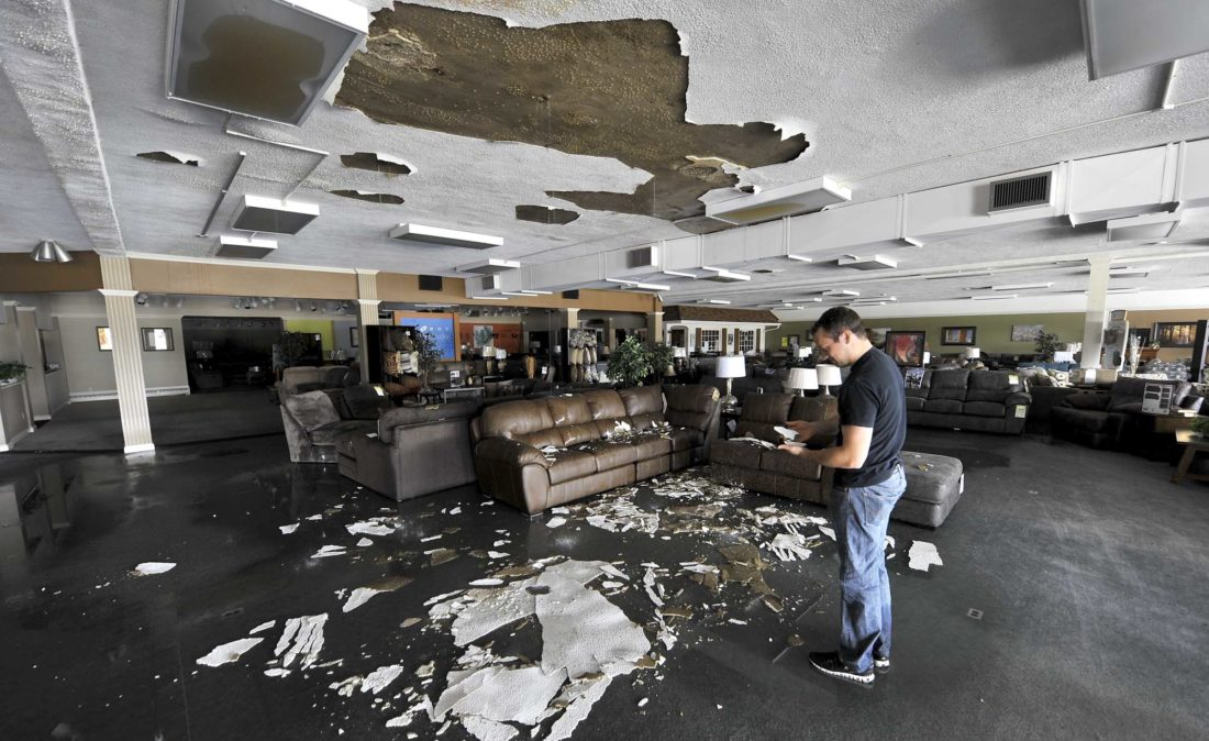 -Messenger photo by Hans Madsen  Justin Mikos looks over a piece of fallen ceiling Wednesday morning as water continues to pour into Mikos and Mikes Furniture store after the a large section of the roof was damaged in Tuesday night's storm.