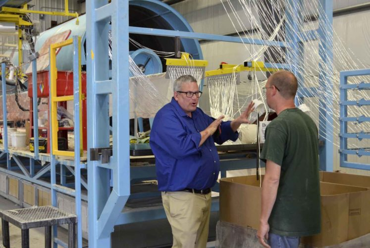 -Messenger photo by Kriss Nelson   Bill Northey, Iowa secretary of agriculture,  gets a tour of the Precision Tank and Equipment manufacturing facility by plant manager Doug Hepperle, who is showing Northey the mold release used for manufacturing fiberglass tanks.
