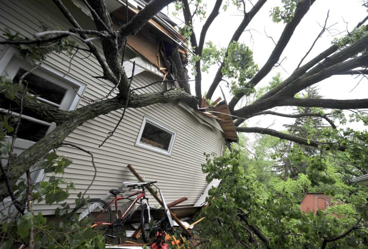 -Messenger photo by Hans Madsen  A bike stands undamaged at the Heather and Anthony Baadke home in the 1600 block of North 23rd Street Wednesday morning after two large trees fell on it during Tuesday night's storm. Branches of the trees went through the roof and into the family's living room.