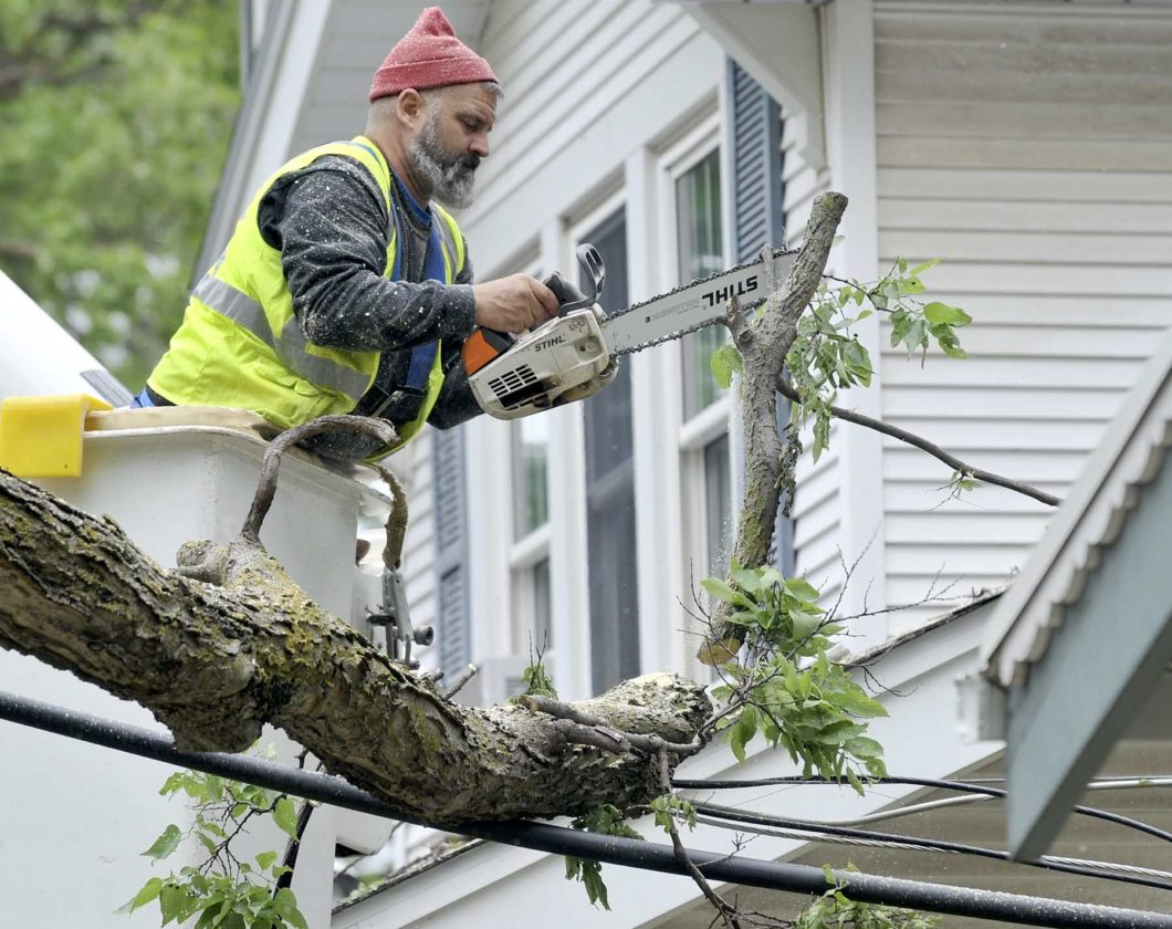 -Messenger photo by Hans Madsen  Will Estlund, owner of Estlund Construction Service, gingerly uses the tip of his chainsaw to pull a just cut branch off a powerline between two homes in the 500 block of South 13th Street Thursday afternoon. The tree blew down in Tuesday's storm.