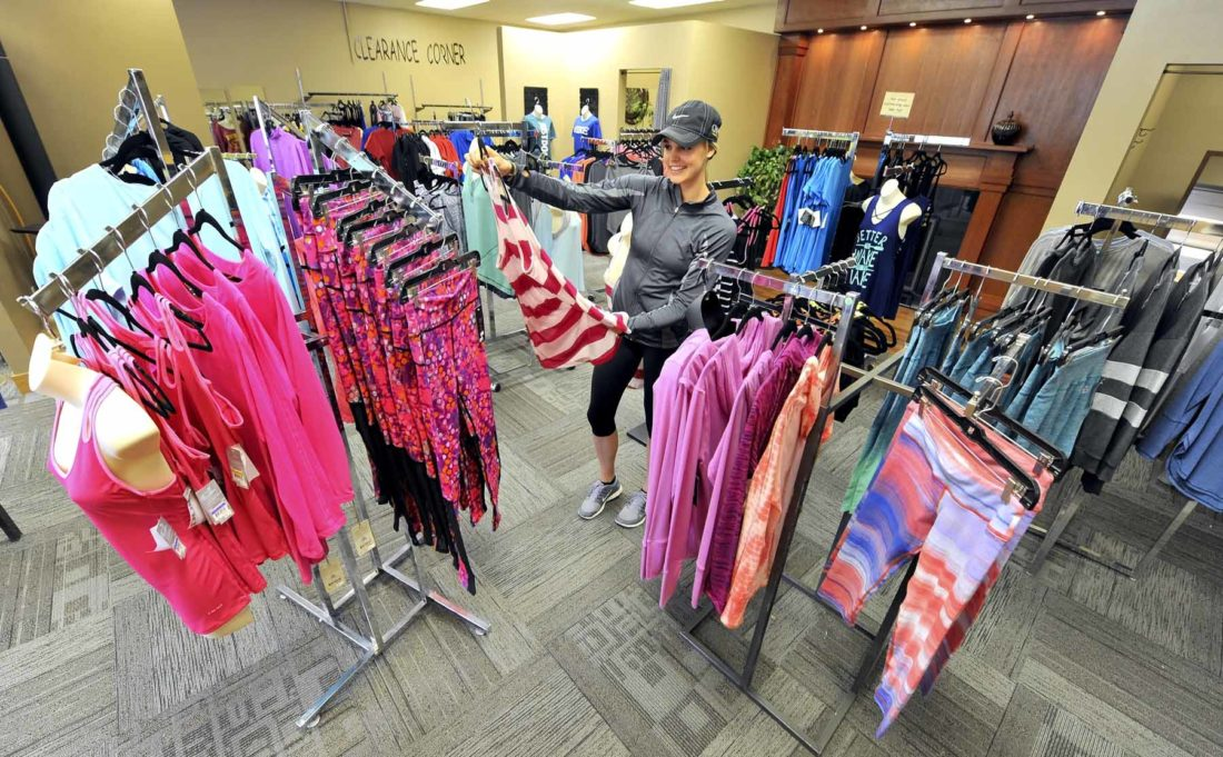 -Messenger photo by Hans Madsen  Amanda Bush, owner of Fit This Casual and Activewear, looks over some of the many items available in her shop. Bush celebrated her grand opening on April 8. She's located at 1208 First Ave. S. in Fort Dodge.