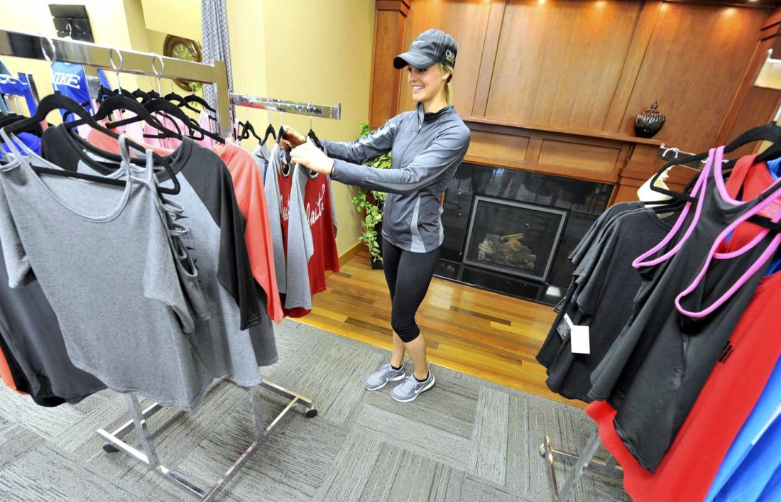 Amanda Bush, owner of Fit This Casual and Activewear, looks over some of the many items available in her shop. Bush celebrated her grand opening on April 8. She's located at 1208 First Ave. S. in Fort Dodge. Rich Sells, who owns the building, still has some of his fireplaces on display in the store, making for a cozy environment.