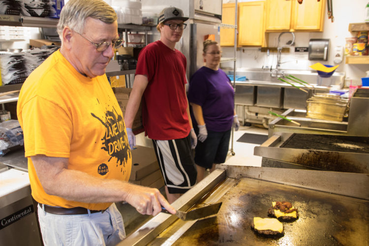 -Messenger photo by Darcy Dougherty Maulsby  Larry Irwin, owner of the Lake City Drive-In, offers some tips to his staff on how to cook a great cheeseburger.