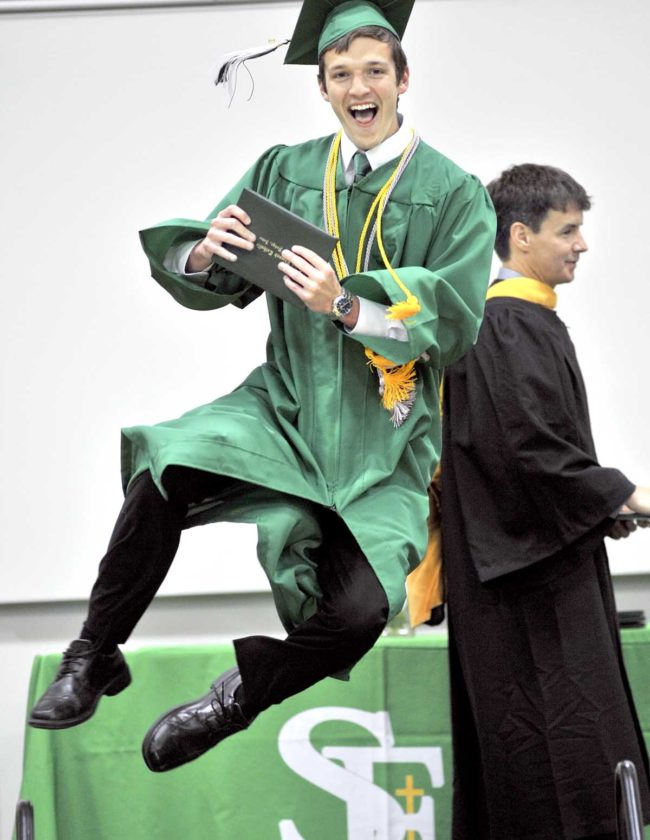 -Messenger photo by Hans Madsen  Nicholas Simpson jumps for joy Sunday afternoon after getting his diploma during the 62nd annual commencement at St. Edmond Catholic School. Ben Crimmins, chair of the St. Edmond School Board, is at right getting ready to hand out another diploma.