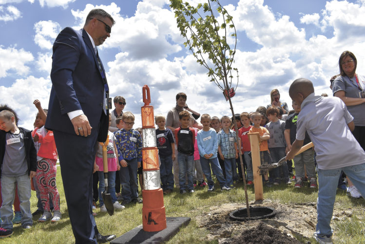 -Messenger photo by Chad Thompson  Jamarco George, 6, a kindergartner at Butler Elementary School, right, lets the dirt slide off his shovel during the annual tree plant at the Fort Dodge Middle School Monday afternoon. Doug Van Zyl, FDCSD superintendent, watches at left.