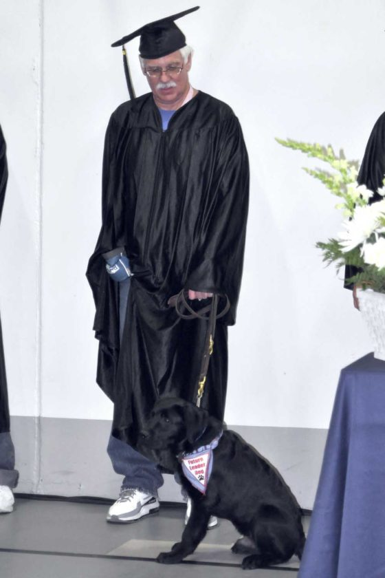 -Messenger photo by Peter Kaspari  Kevin Voyna, a Fort Dodge Correctional Facility inmate, stands with his Leader Dog, Bill, as he waits for his name to be called at graduation. Voyna completed the culinary baking program offered to inmates through Iowa Central Community College.
