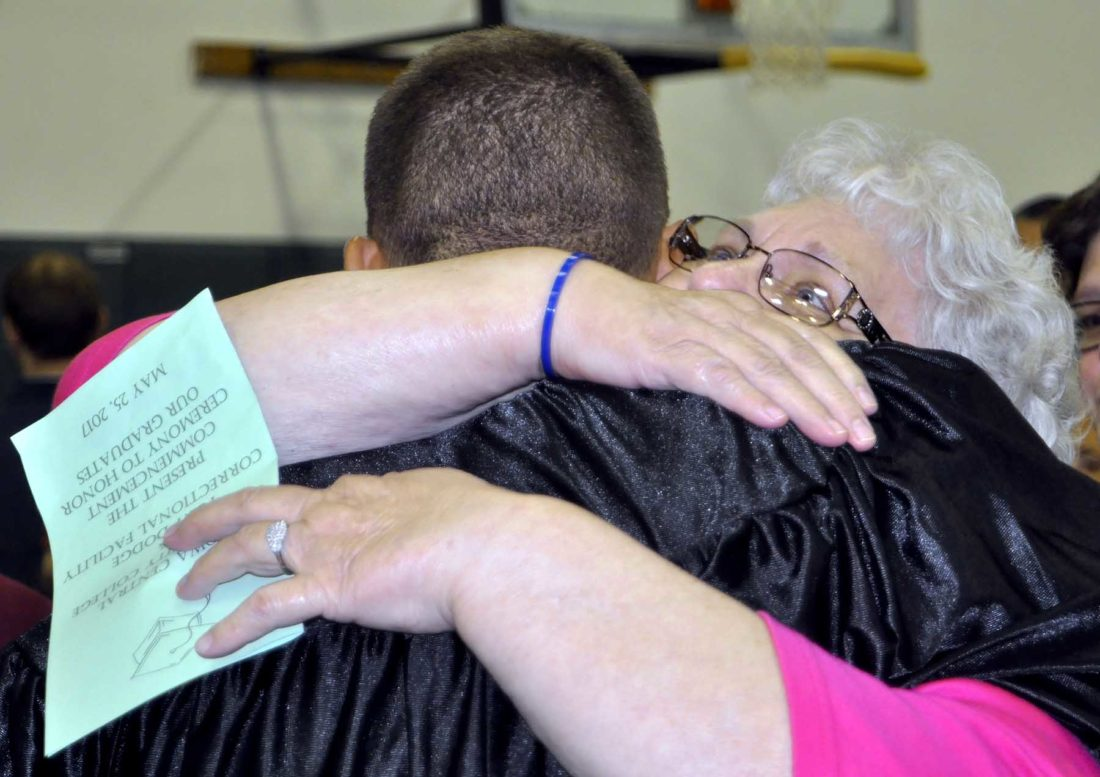 -Messenger photo by Peter Kaspari  Kodi Hettinger, left, an inmate at Fort Dodge Correctional Facility, gets a hug from his grandma, Donna Fischer, at his graduation ceremony Thursday.