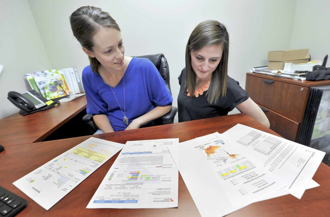 -Messenger photo by Hans Madsen  Jill Nelson, Greater Fort Dodge Growth Alliance community development director, at left, along with Office Manager Kate Stucky look over some of the savings on the Growth Alliance's utility bills.