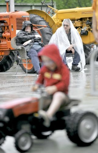 -Messenger photo by Hans Madsen  Sheryl and Larry McCabe, of Dayton, cover up Saturday as they watch the kiddie tractor pull during the sixth annual Dayton Old Engine Day. They are seated in front of the four tractors they brought to display.