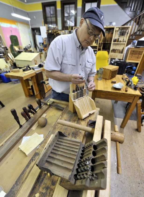 -Messenger photo by Hans Madsen  Rusty Farrington, of Rockwell City, looks over a drill bit case he built based on the design of the antique one sitting on his workbench. He's also crafted a number of tool boxes and cabinets for his own use as well as many objects for family members and his own home.
