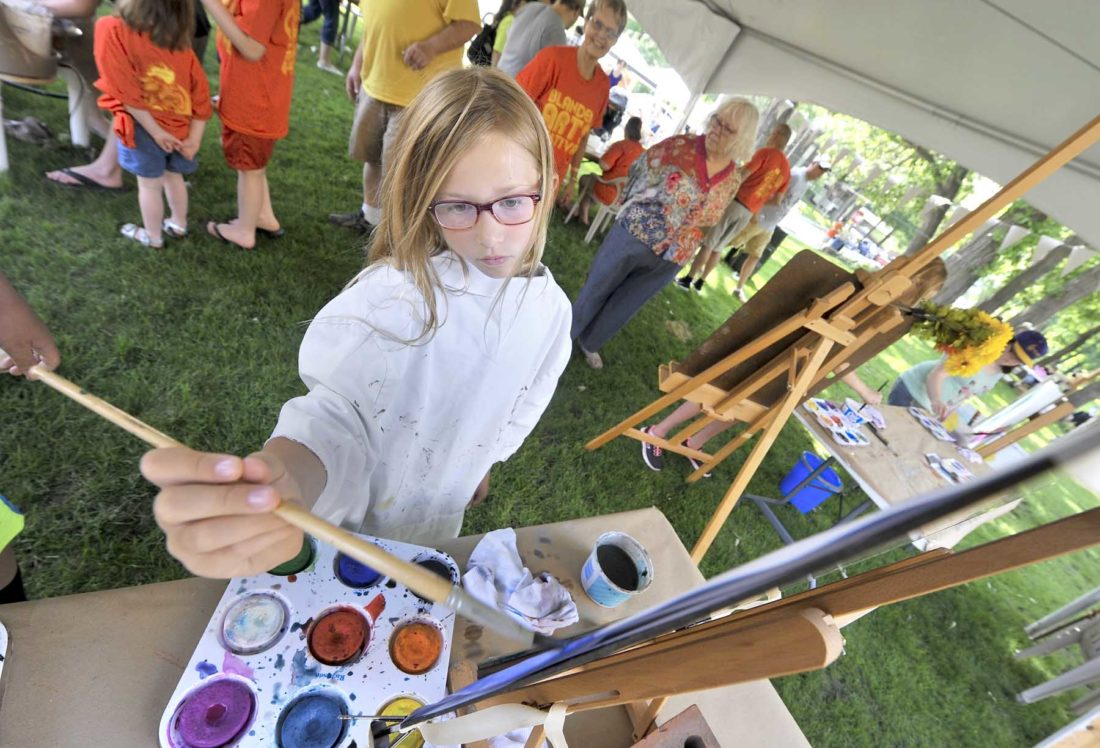 -Messenger photo by Hans Madsen  Wearing an old shirt to cover up her own nice clothes, Tristen Holst, 9, of Fort Dodge, works on a painting Saturday morning during the Blanden Memorial Art Museum Summer Arts Festival. Holst was one of the receipients of an art scholarship at the event.